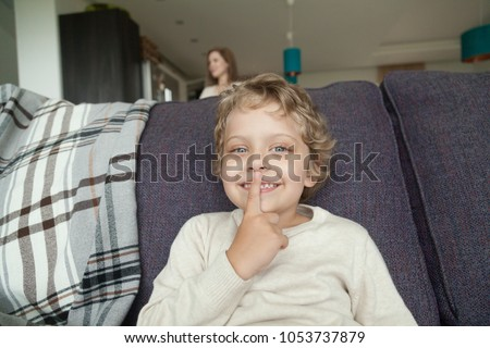 Kid boy holding finger on lips hiding on sofa from mom searching son at home, cute quiet child playing hide and seek game sitting on couch waiting for mom to find him, family fun activity concept