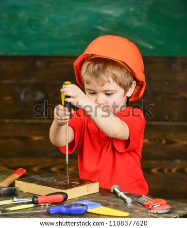 Kid boy holds screwdriver tool. Toddler on busy face plays with screwdriver at workshop. Child in helmet cute playing as builder or repairer, or handcrafting. Handcrafting and workshop concept.