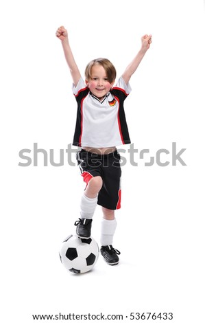 Kid / Boy in complete german soccer outfit raises his arms. He is the winner.