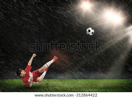 Kid boy kicking soccer ball at stadium field