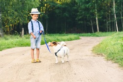 Kid boy learning how to tame and train a dog walk on leash