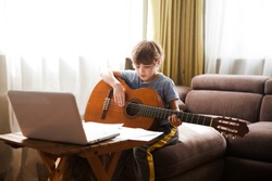 Kid  boy playing  guitar and watching  online lessons  on laptop while practicing at home.  Stay home. quarantine. Online training, online classes.