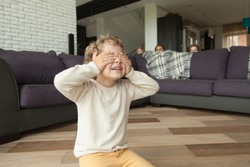Kid boy playing hide and seek game at home, child closing eyes with hands counting while parents and sister hide behind sofa in living room peeking out, happy family having fun with children concept