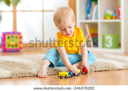 kid boy playing toys at home or kindergarten