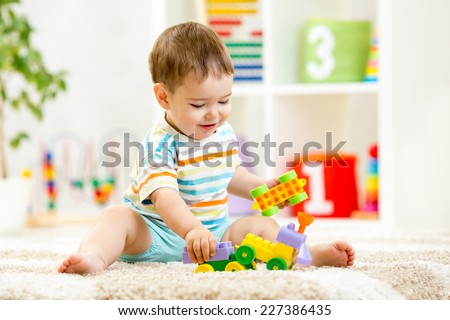 kid boy playing with building blocks at home or kindergarten #227386435