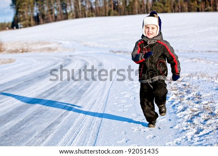 Kid boy running along the road with snow in winter