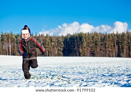 Kid boy running on field with snow in winter