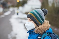 Kid boy wearing ffp medical mask on the way to school. Child backpack satchel. Schoolkid on cold autumn or winter day with warm clothes. Lockdown and quarantine time during corona pandemic disease