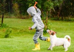 Kid boy wearing waterproof coat playing with dog under rain