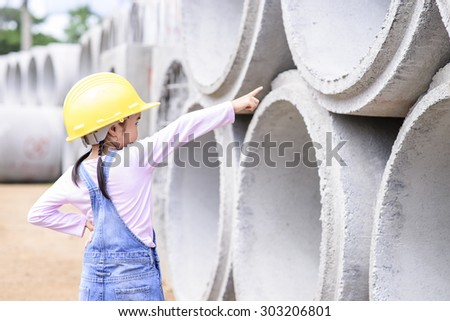 Kid civil engineer inspecting  huge concrete pipe and point to it