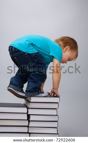 Kid climbing on top of the books pile describing education efforts