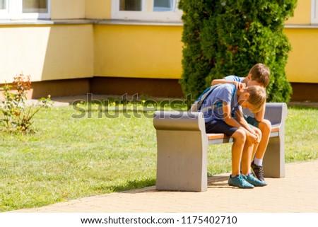 Kid comforting consoling upset sad boy in school yard