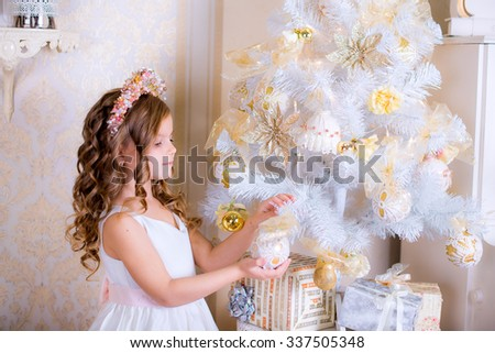 kid decorate white Christmas tree golden balls