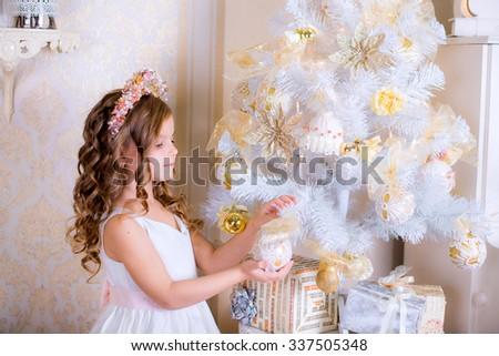 kid decorate white Christmas tree golden balls