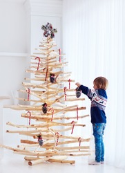 kid decorating the eco friendly, reusable christmas tree, with pine cones and christmas candy canes