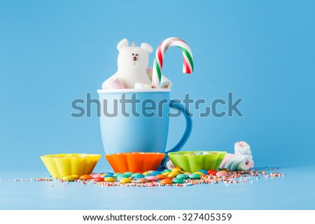 Kid decoration. Colored candy and mug with toy on blue background