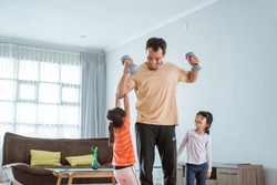kid disturb his daddy while doing sport at home