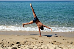 kid does acrobatics on the beach