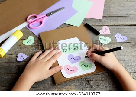 Kid Doing A Greeting Card Holds Black Marker In Hand And Writes Wishes