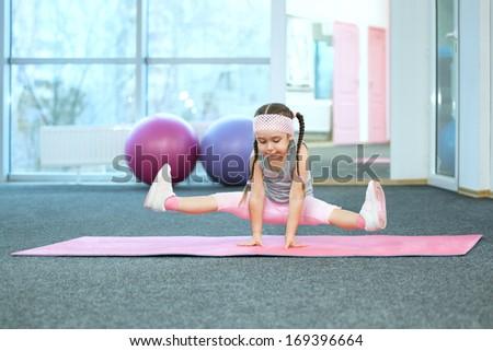 Kid doing fitness exercises on the mat