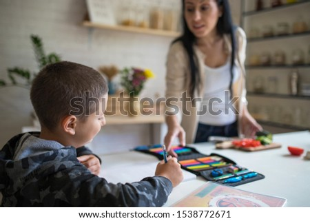 kid doing homework in the kitchen while mom prepares lunch