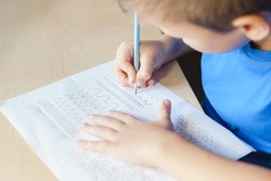 Kid doing lesson at home. Child boy writing in worksheet with pencil. Children education concept