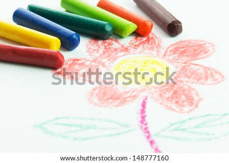 Kid drawing flower picture using crayons on white background