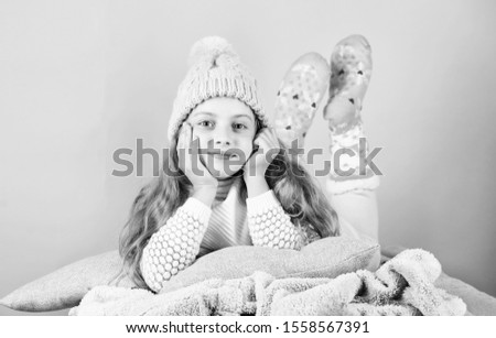 Kid dreamy face wear knitted accessory. Kid girl wear cute knitted fashionable hat and scarf accessory. Winter fashion accessory. Winter accessory concept. Girl long hair dream pink background.