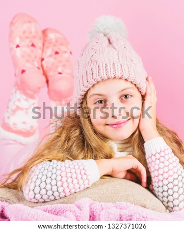 Kid dreamy face wear knitted accessory. Winter fashion accessory. Kid girl wear cute knitted fashionable hat and scarf accessory. Winter accessory concept. Girl long hair dream pink background.