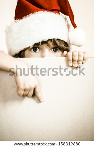 Kid dressed in Santa Claus with paper blank. Christmas holidays concept