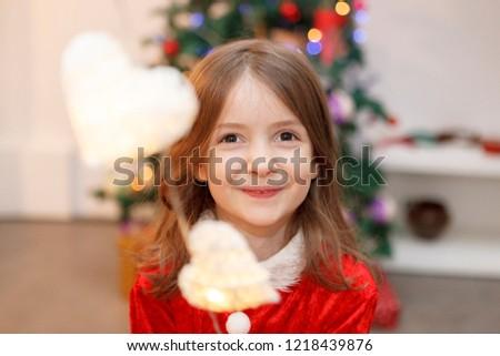 kid dressed like santa with light heart shaped decoration