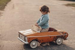 Kid driving a toy car
