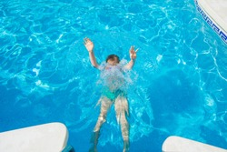 Kid drowns in the pool. Child drowning in water. Boy does not know how to swim and drowns