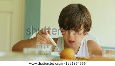 Kid eating gnocchi closeup. Young boy eats food