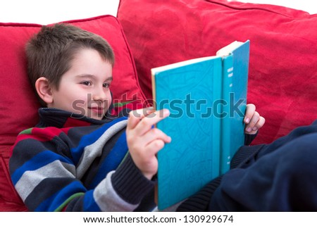 Kid enjoy reading the novel on the comfortable red couch.