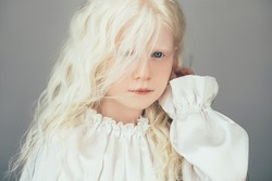 Kid fashion portrait. Child beauty. Precious innocence. Portrait of sweet albino blonde small girl with curly hair blue eyes in white vintage blouse isolated on gray background.