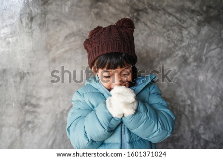 Kid feeling expression concept. Asian child girl wear winter coat jacket fells very cool during winter season. Small girl shiver in cold weather headwear. Foto stock ©