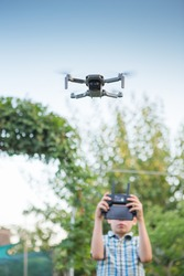 Kid flying drone. Boy operate drones. Child Operating Quadcopter. Little Pilot Using Drone Remote Controller