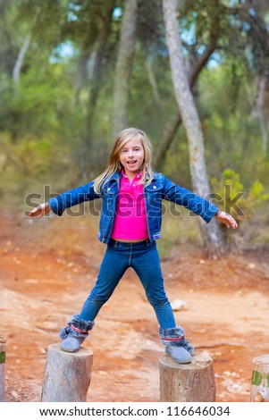 kid girl climbing tree trunks with open arms having fun in the pine forest