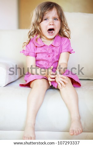 Kid girl cries sitting on the sofa