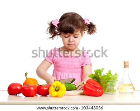 Kid girl cutting cucumber for salad. Concept healthy food.
