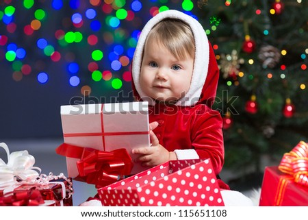 kid girl dressed as Santa Claus near Christmas tree with gifts