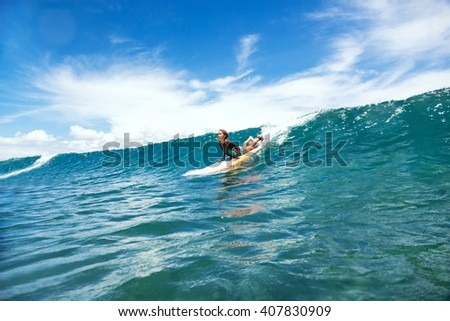 Kid girl is learning surfing, riding a wave #407830909