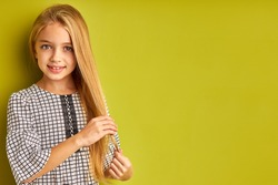kid girl is touching her long blond hair, enjoy having perfect hair, look at camera isolated over green background