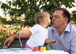 kid girl learning painting with father. daughter kisses dad.