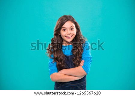 Kid girl long hair posing confidently. Girl curly hairstyle feels confident. Child hold hands confidently crossed chest. Child psychology and development. Confident posture. Upbringing confidence.
