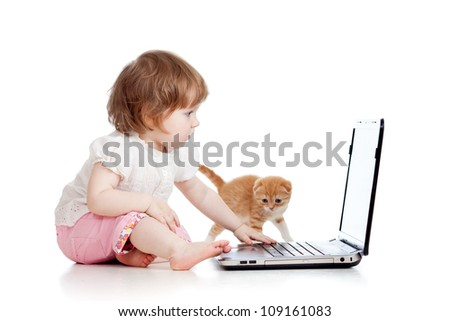 kid girl playing with kitten and using laptop