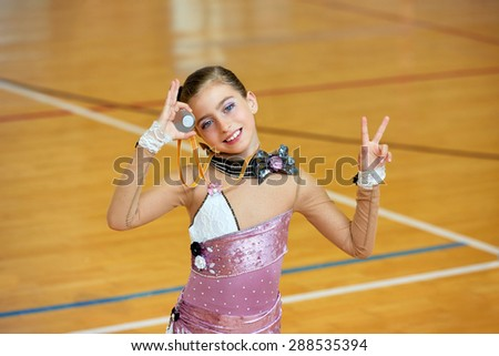 kid girl rhythmic gymnastics on wooden deck medal winner gesture