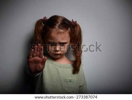 Kid girl showing hand signaling to stop violence and pain and looking down on dark background with empty copy space