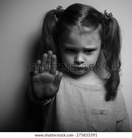 Kid girl showing hand signaling to stop violence and pain and looking down with sad face. Black and white portrait in dark shadow